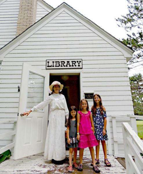 Girls posing with costumed re-enactor at Dakota City Heritage Village Library